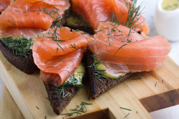 Homemade gravlax, smoked salmon with mustard sauce and dill  on toasted rye bread