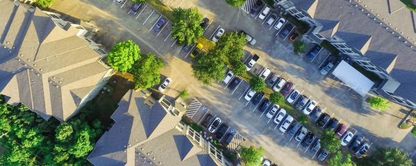 Panorama aerial view of apartment garage with full of covered parking, cars and green trees of multi-floor residential buildings in Houston, Texas, US. Urban infrastructure, transportation concept