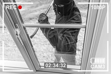 CCTV view of burglar breaking in to home through window - fototapety na wymiar
