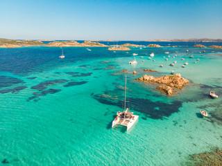 Drone aerial view of catamaran sailing boat in Maddalena Archipelago, Sardinia, Italy. Maddalena Archipelago is composed of Razzoli, Santa Maria and Budelli islands.