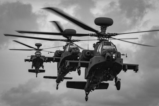 A line of three WAH-64 Apache Longbow attack helicopters coming into land, RAF Shawbury, Shropshire