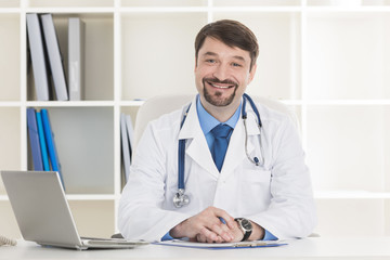 Male doctor working at office desk