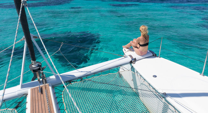Woman in bikini tanning and relaxing on a summer sailin cruise, sitting on a luxury catamaran in picture perfect turquoise blue lagoon near Spargi island in Maddalena Archipelago, Sardinia, Italy.