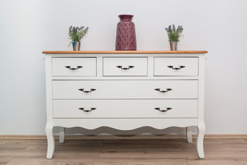 White wooden dresser with three vases and flowers on white wall background. Chest of drawers close...