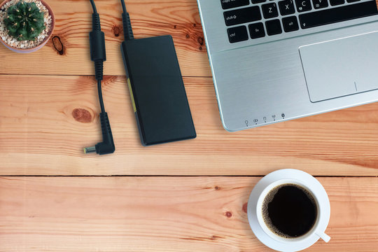 Adapter power cord charger of laptop computer with black coffee in white cup and cactus on wooden floor,Top view