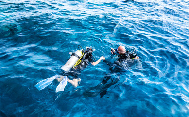 diving instructor holding a disciple's hand in blue water Wall mural