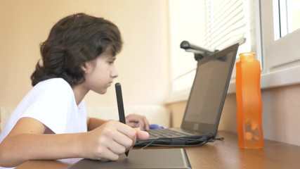 handsome modern boy teenager working on a graphic tablet. he looks at the laptop screen.