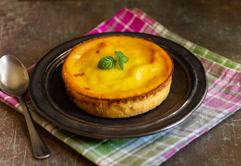 Fresh homemade creamy tart, on rustic dishware, napkin and background.