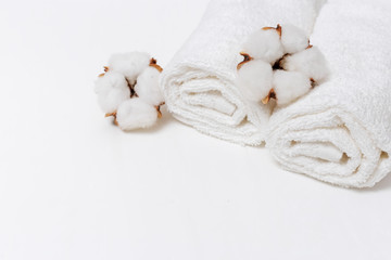 Relaxing spa resort background with cotton flowers and  white towel. Copy space. Selective focus.