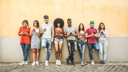 Multiracial friends using smartphone against wall at university college backyard - Young people addicted by mobile smart phone - Technology concept with always connected millennials - Filter image Wall mural