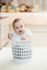 Little kid sitting in an office trash can, girl
