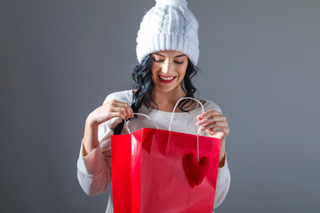 Happy young woman holding a shopping bag on a gray background