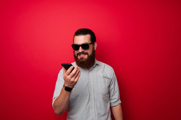 Bearded man using phone over red background