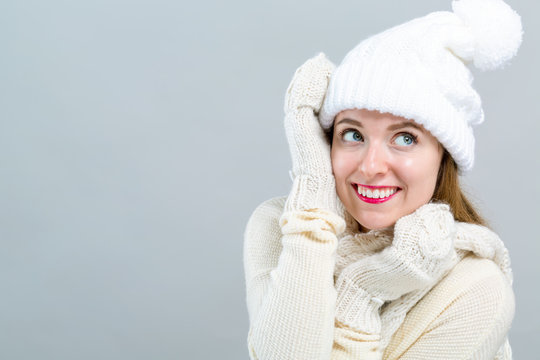Young woman in a cold weather winter outfit on a gray background