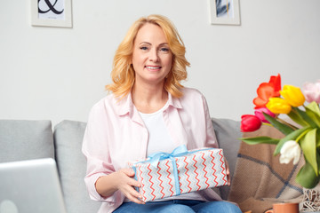 Senior woman at home celebration sitting holding gift smiling happy