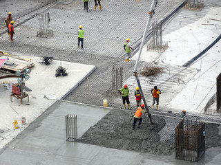 KUALA LUMPUR, MALAYSIA -AUGUST 27, 2018: Concreting work by construction workers at the construction site. Heavy machinery used to carry wet concrete to the pouring location.
