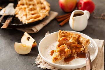 Slice of freshly baked apple pie with caramel sauce and cinnamon