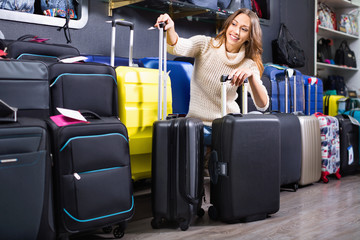 Female customer choosing travel suitcase