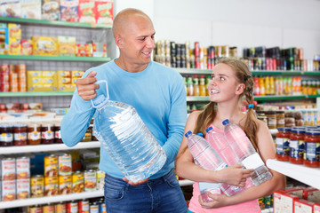 Friendly father with tween girl purchasing together water in bottles