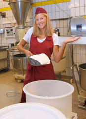 A young woman takes up her work in a bakery. She  poses for the camera and shows her various types  of bakery workflows.