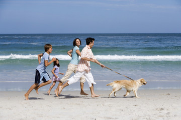 Family exercising pet dog running along beach by sea on vacation