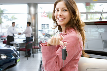 Couple buying new car with smiling woman holding car key in showroom at camera