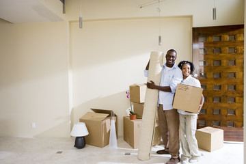 Portrait of couple moving in carrying boxes and rug into new home