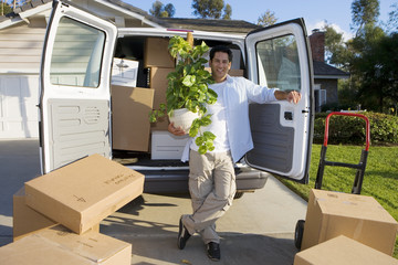 Smiling man moving house in rear of van with pot plant at camera