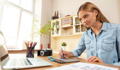 Woman graphic artist uses a graphic tablet