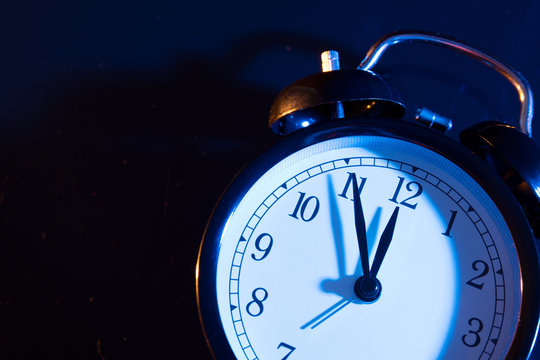 Five minutes to midnight on retro analog clock