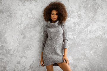 Young black woman wear high-neck wool and cashmere oversized sweater Wall mural
