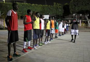 Sudanese refugees line up ahead of a basketball game in Cairo