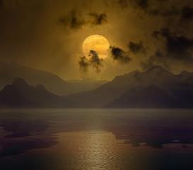 Rising orange full moon in dark night sky with reflection in water