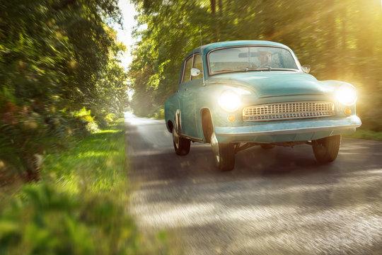 Oldtimer fährt auf einer sonnigen Waldstraße