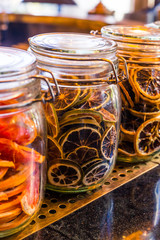Sliced dry orange in the glass jar as ingredient for drinks and autumn, winter decoration