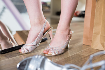 Customer is trying on brilliant heeled sandals near mirror