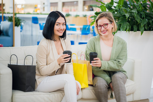 Two young women having coffee break together at shopping mall