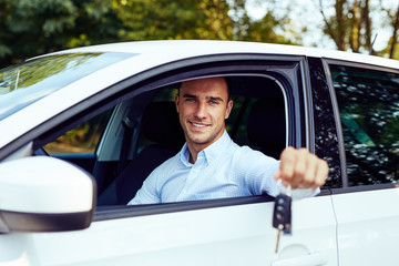 Smiling man sitting in his car and holding keys