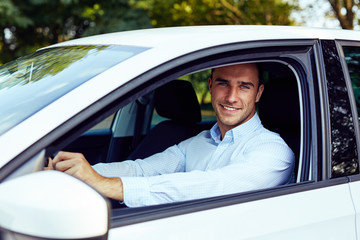 Smiling man sitting in his car, young driver