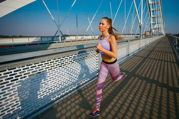 Young sports woman  jogging on the bridge