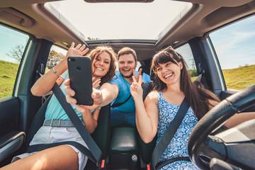 road trip group of people making selfie in the car
