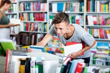 Boy teenager choosing new book in shop