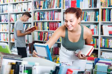 girl teenager choosing book in shop .
