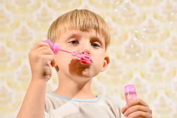 The boy blows soap bubbles, close-up.