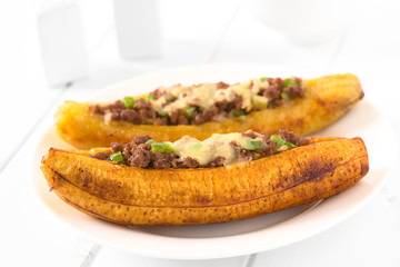 Baked ripe plantain stuffed with mincemeat, olive, green bell pepper and onion, sprinkled with cheese, a traditional dish in Central America called Canoa de Platano (Plantain Canoe) (Selective Focus)
