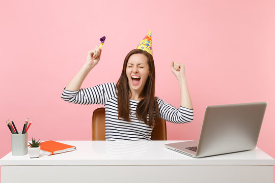 Cheerful girl with closed eyes in birthday party hat with playing pipe screaming celebrating while sit work at desk with pc laptop isolated on pink background. Achievement business career. Copy space.