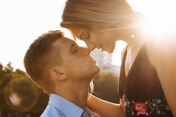 the couple kisses, and between them the rays of the sun, the sun, the light. attraction between a man and a woman. kiss in the sun. kiss the sun. between us is the sun.