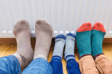 Family wearing colorful of pair woolly socks warming cold feet in front of heating radiator at home.