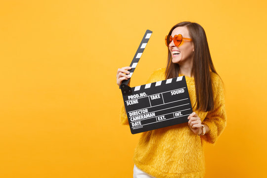 Laughing young woman in orange heart eyeglasses looking aside and holding classic black film making clapperboard isolated on yellow background. People sincere emotions, lifestyle. Advertising area.