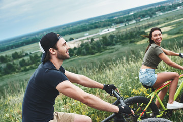 A man and a woman are laughing and cycling. Close up view